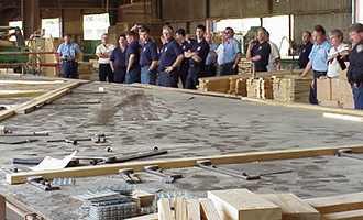 Group of firemen in t-shirts and jeans standing at a large table where trusses are built