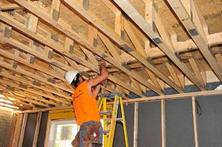 A construction worker on a ladder works on the interior of a second floor truss