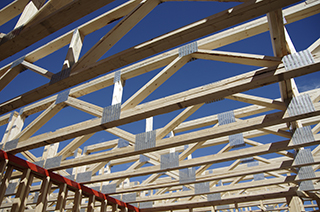 Skyward view of second story trusses with the blue sky behind them