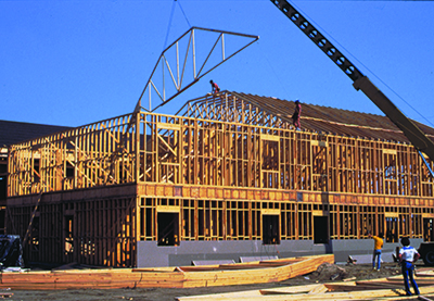 A crane lowers a roof truss into place on top of a second story building
