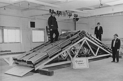 Black and white photograph of a set of roof trusses sitting on the floor with loads and two men standing on top and one man in front of the trusses