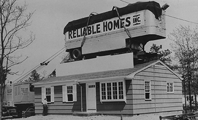 A locomotive train car that reads Reliable Homes Inc sits on top of a single story house