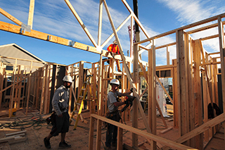 Three construction workers help to attach a roof truss to a building structure