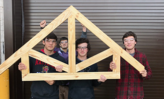 Four students wearing eye protection hold up a roof truss example that they built