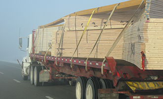 Truck driving on the road is hauling trusses for a delivery