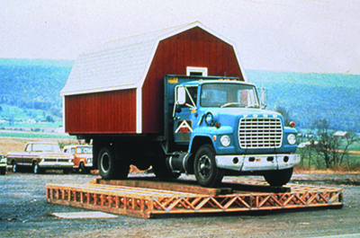 A blue truck with a white and red shed in the truck bed is on top of a set of floor trusses that are on the ground