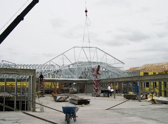 A steel roof truss is put into place on a new building